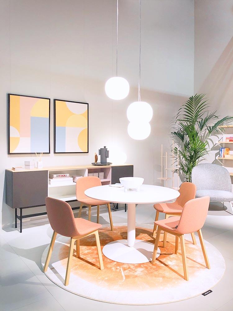 Weißer Runder Esstisch umgeben von Stühlen in Farbe Puder und Bilder in Sonnengelb und Hellblau