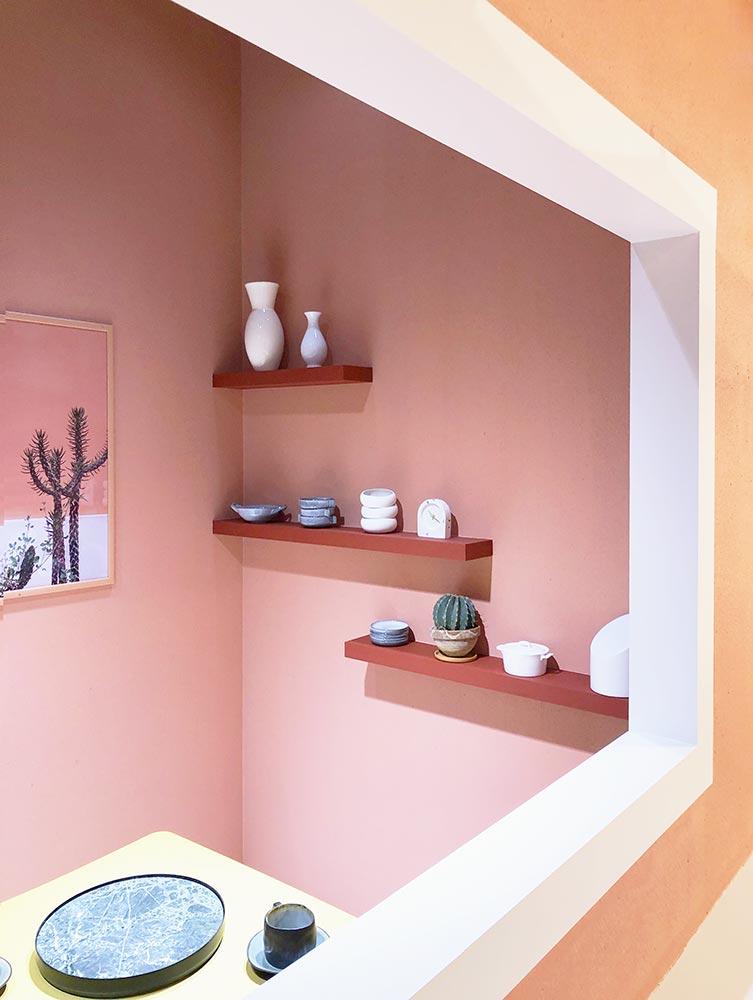 Zimmer in warmen Farben mit schlichten Regalen und weißen Vasen darauf