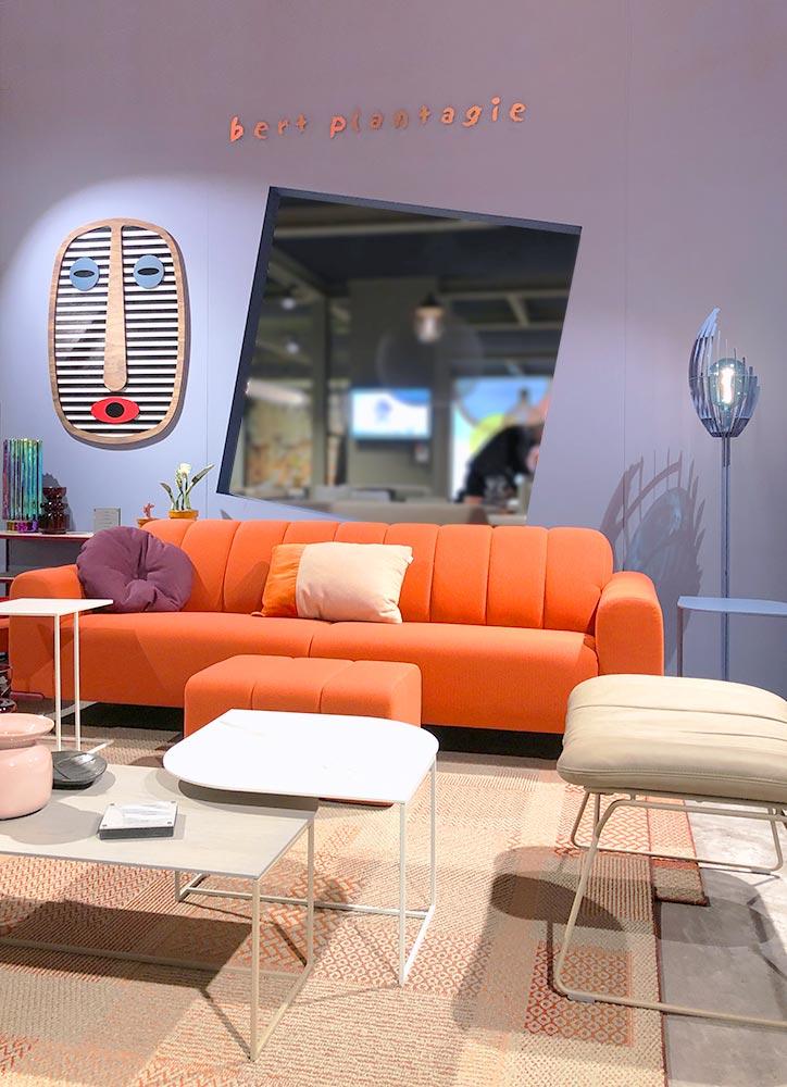 Einrichtungsszene in warmen Farben mit Sofa in kräftigem Orange vor einer fliederfarbenen Wand