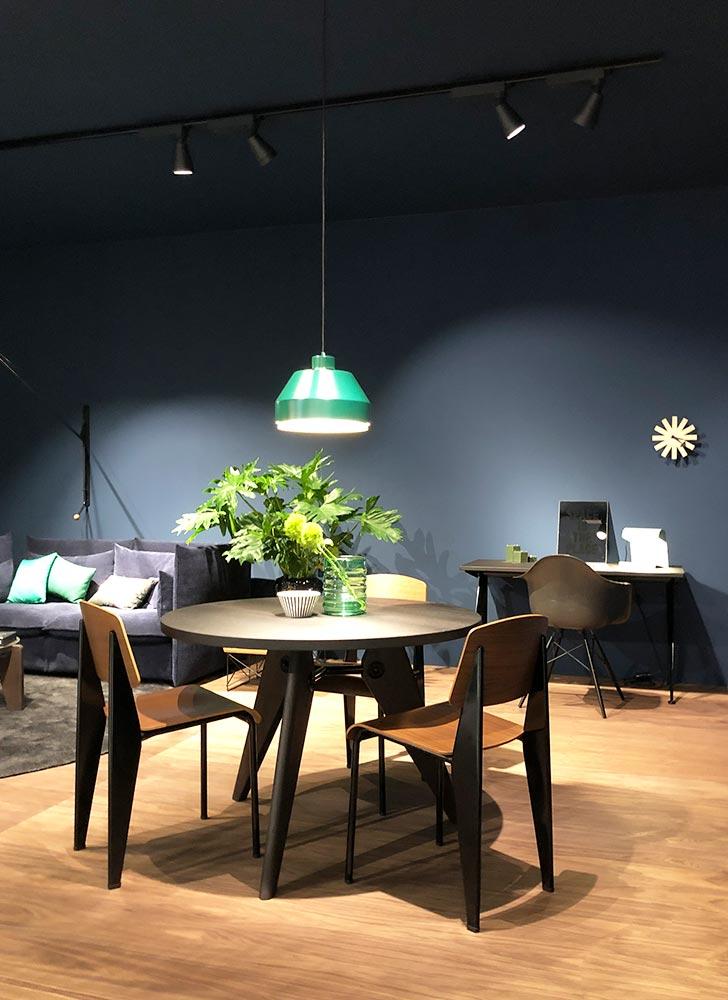 Einrichtungsszene mit Tisch und Stühlen aus Holz vor dunkelblau gestrichener Wand